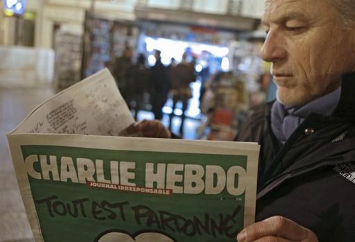 1月14日、フランス南東部ニースで週刊紙シャルリエブドを読む人(AP=共同)