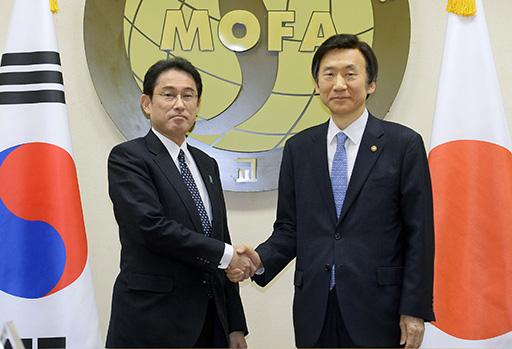 2015年12月、日韓外相会談を前に韓国の尹炳世外相(右)と握手する岸田外相=ソウルの韓国外務省(共同