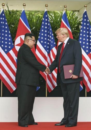共同声明に署名後、握手する北朝鮮の金正恩朝鮮労働党委員長(左)とトランプ米大統領=6月12日、シンガポール(ロイター=共同)