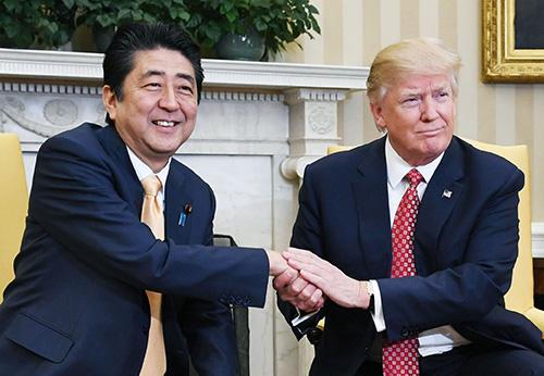 2月の日米首脳会談でトランプ米大統領(右)と握手する安倍首相=ワシントンのホワイトハウス(共同)